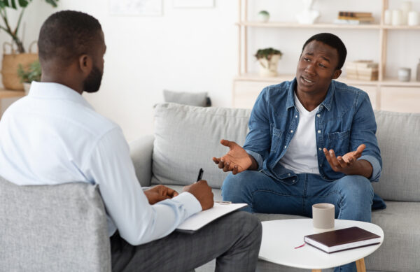 Stressed black man explaining his problems to psychologist at individual therapy session at office, copy space